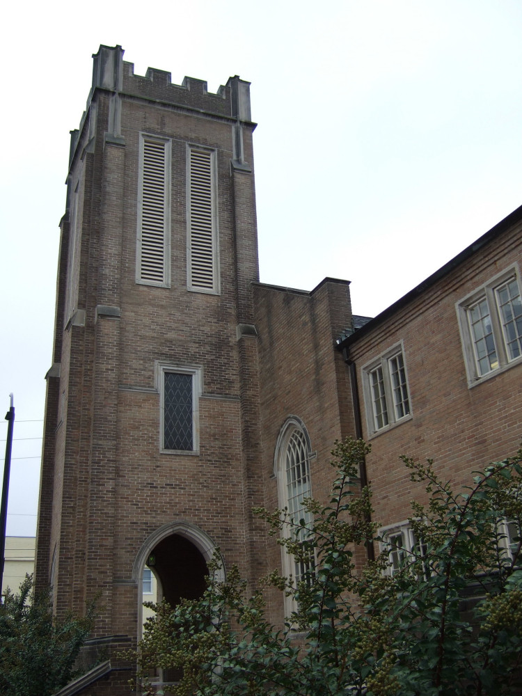 Simple, square brick tower attached to a church building with rectangular crenelations on top