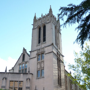 Gothic revival tower with rectangular windows at corner of a campus building, looking over concrete and brick pedestrian steps