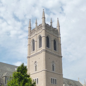 A stone gothic revival tower attached to a large church, overlooking a courtyard