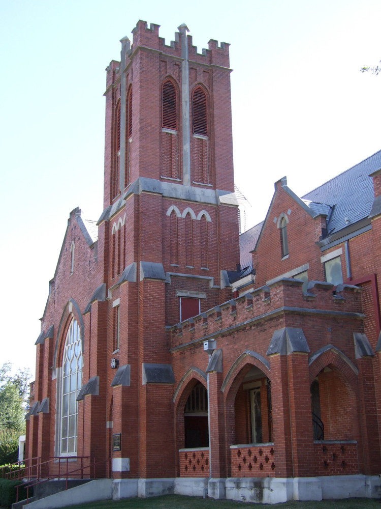 Brick gothic revival church with a square brick tower