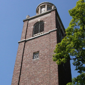 A very tall, simple square, brick tower with a rounded white lantern at the top
