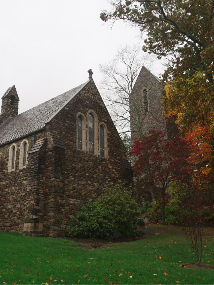 Simple stone church with arched windows and a detached square stone tower with a peaked roof in the fog