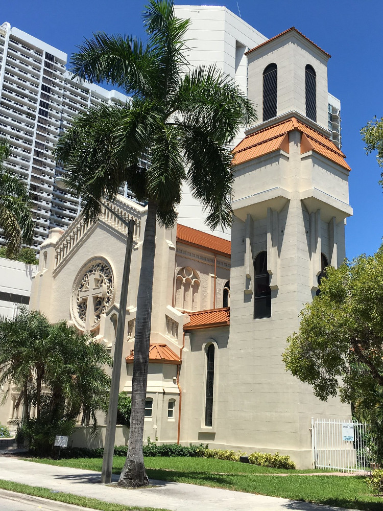 A white, medium sized Romanesque cathedral with balustrades and attached tower in a modern style, with sloped metal roof, in an urban setting with palm trees