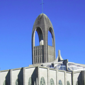 Tall brutalist tower with an arched top adjacent to a brutalist monastery chapel and colorful garden