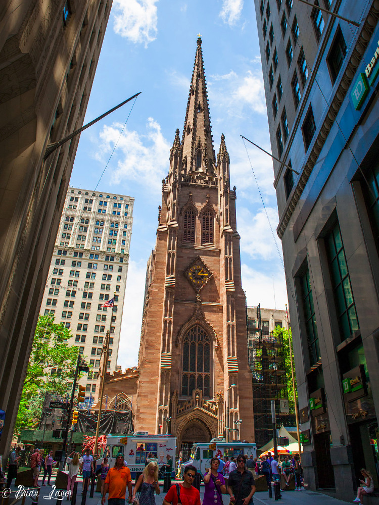 Large historic, urban, red stone church with an ornate gothic revival tower overlooking a narrow city street with skyscrapers