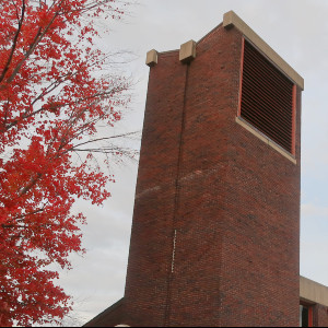Simple, plain, nearly featureless contemporary brick tower with a angular roof and metal vents at the belfry on one side wall