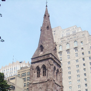 Tall, stone gothic revival tower with a windowed spire aside a historic stone church in an urban setting