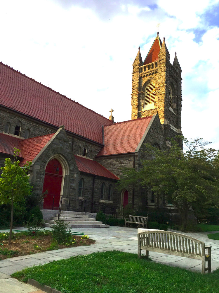 Medium-sized stone church with bright red doors with a small square tower in the back, containing four corner spires and a larger central spire