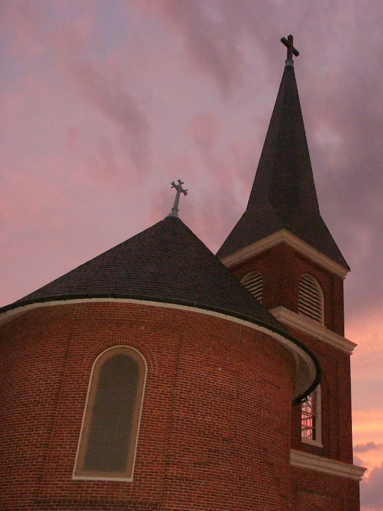 Rear facade of a small brick church with a small tower photographed against a purple and gold sunset