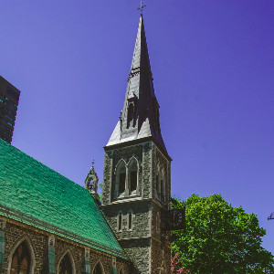 Stone tower and former church in the gothic revival style in an urban setting