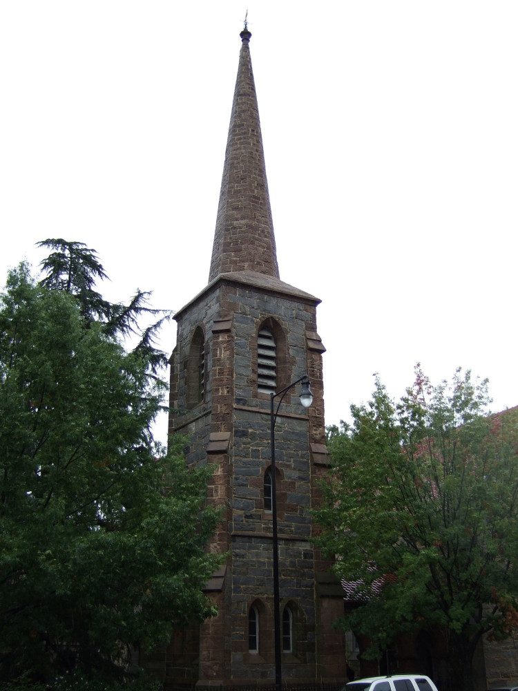 Simple, small, square gothic revival detached tower with a simple stone tower topped by a rooster weather vane