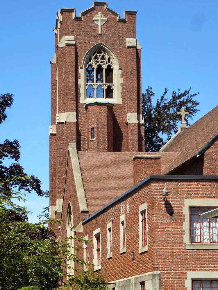 Simple, square brick tower with a large gothic window open to the belfry, attached to a brick church building