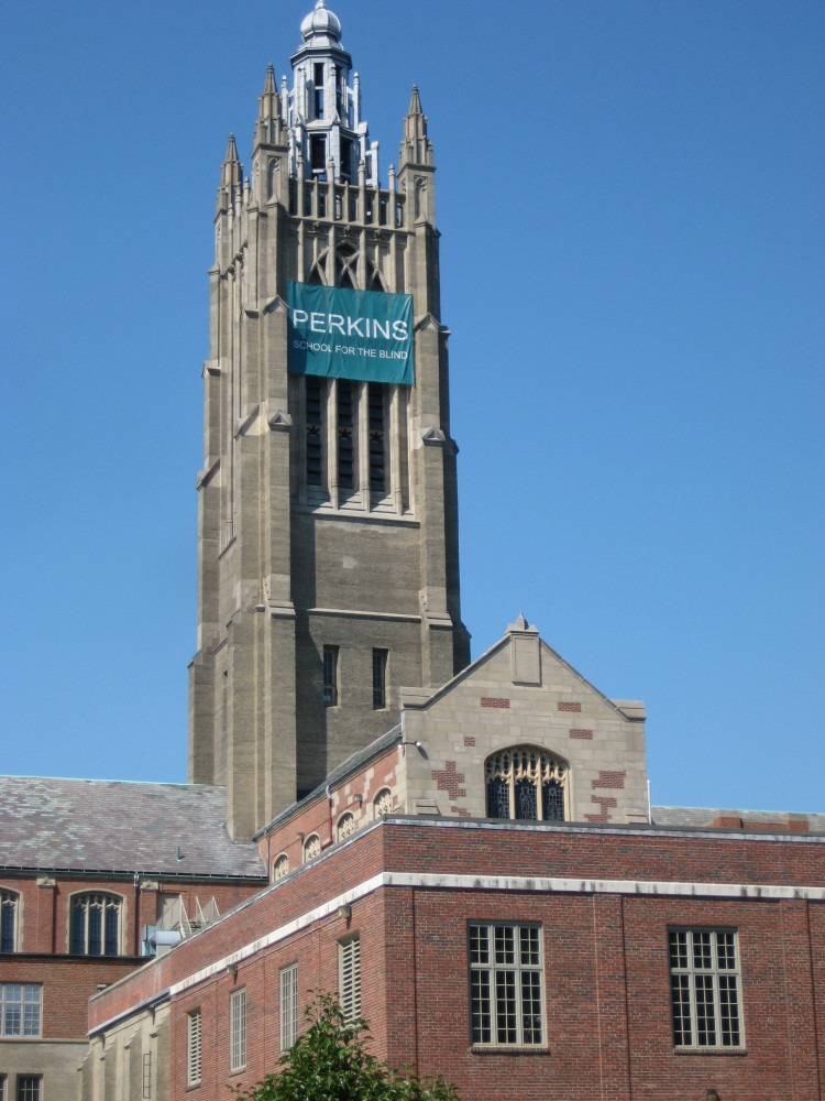 """Large gothic revival tower with unusual lantern top with a banner hanging from it reading, """"Perkins School for the Blind"""""""