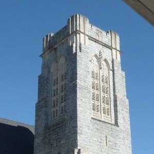 Gray block square tower overlooking a courtyard on the church grounds