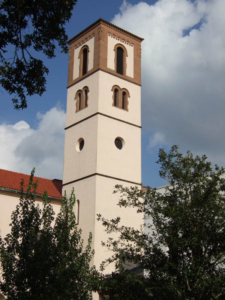 Square cream and clay-colored Romanesque tower attached to a cream-colored church with a barrel tile roof