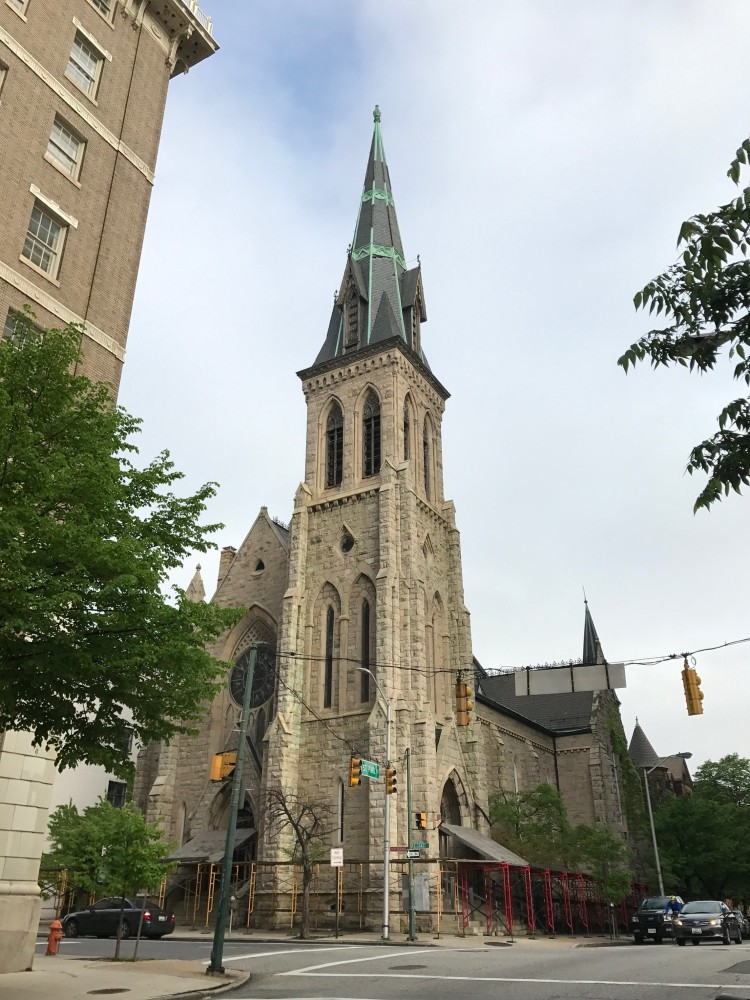 Gothic revival urban church with a tall shingled spire