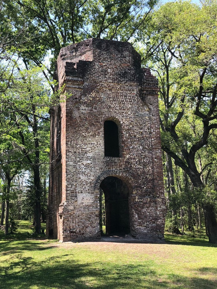 A ruined brick tower standing alone amongst the trees, the steeple long gone