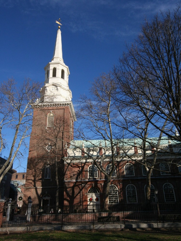 Large colonial brick church with a sturdy brick tower and an imposing white steeple with a lantern and high spire.