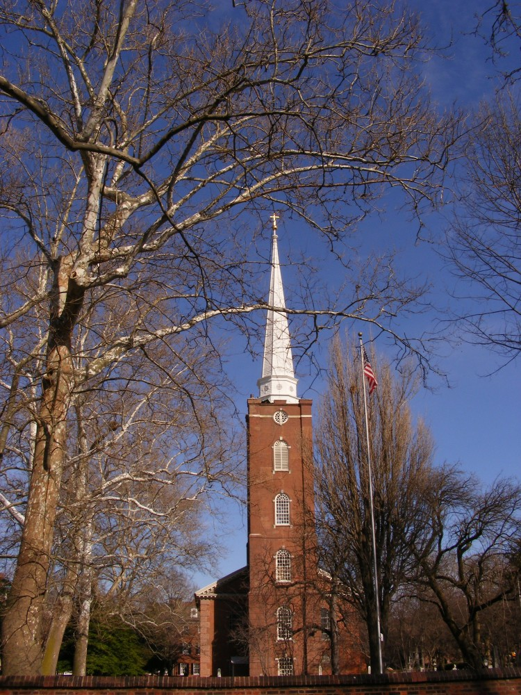 Brick colonial church with a tall, thin, brick tower and a towering white steeple, on a sunny winter day with leafless trees.