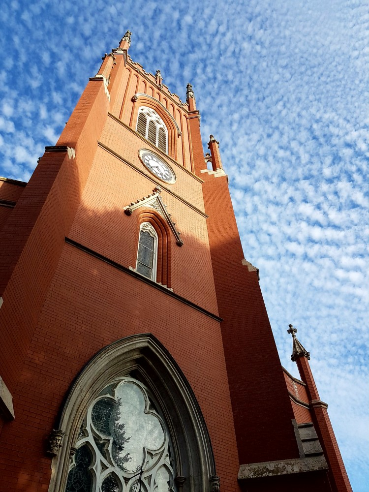 Looking up from below at a brick church bell tower, the upper half illuminated brightly by the sun against a blue sky with high clouds.