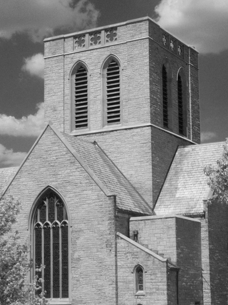 A black and white photograph of a modern, simple square gothic revival tower at the crossing of a church
