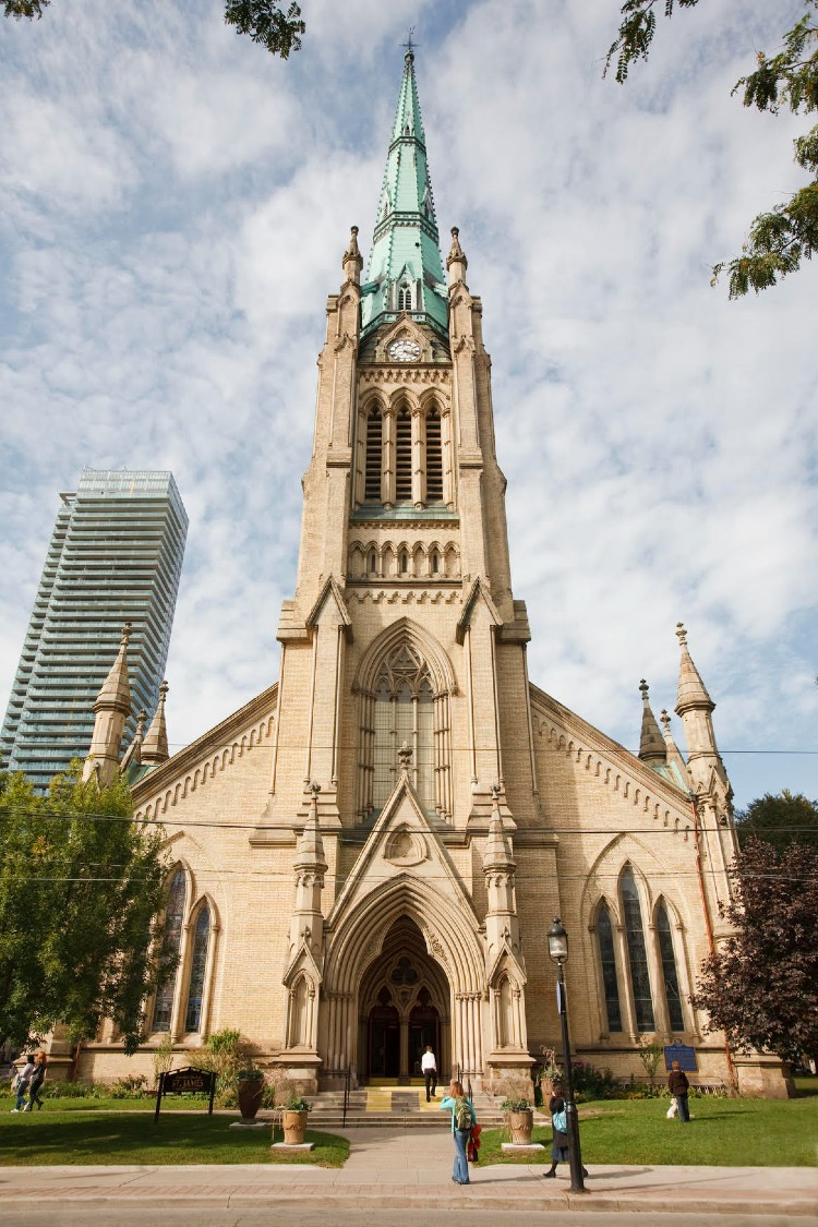 Very tall gothic revival church with a soaring, green copper-plated-spire overlooking urban greenspace