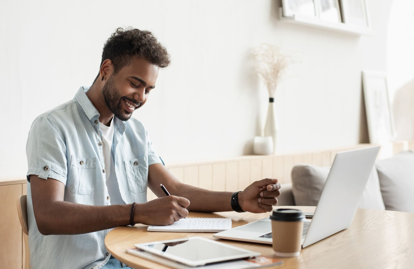 SaaS marketing: Smiling man writing on his notebook with his laptop in front of him