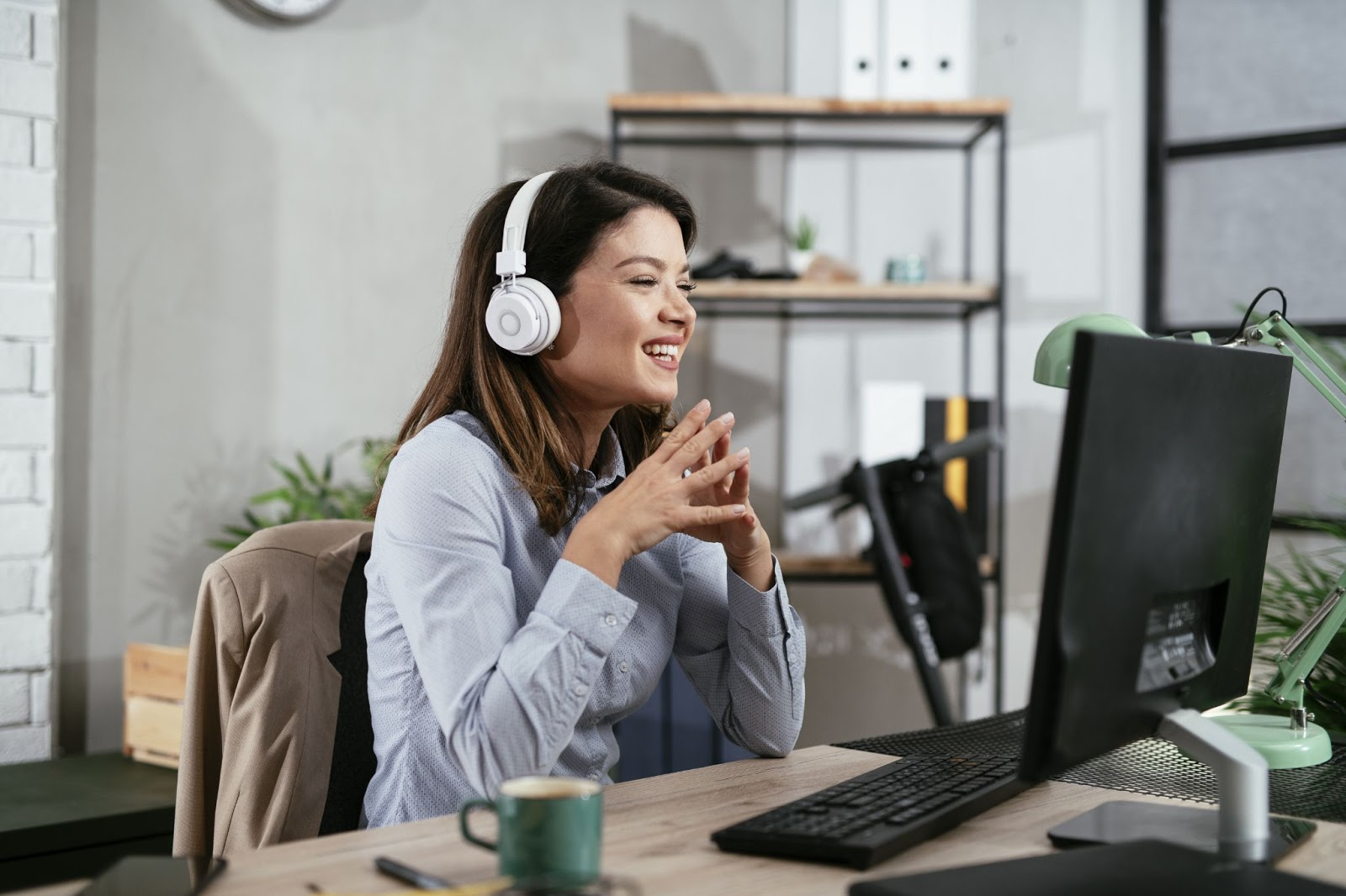 Smiling woman wearing headphones while in front of her computer
