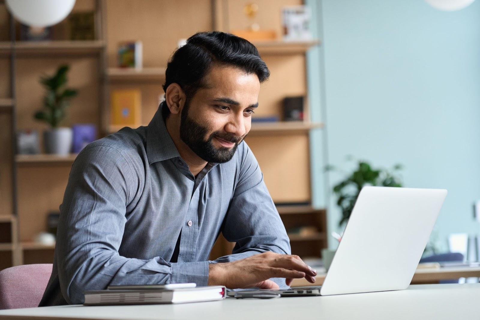 B2B marketing tools: Smiling man working on his laptop