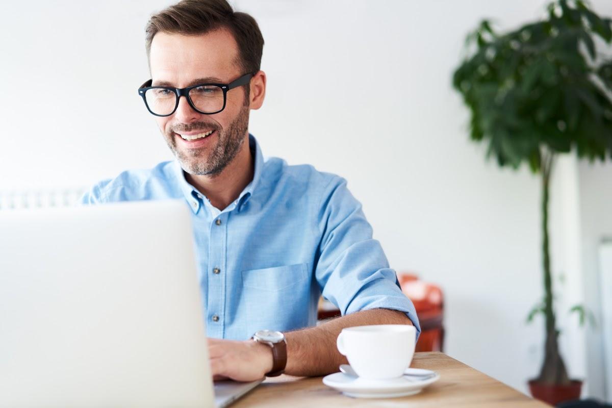 drop surfing: smiling man looking at his laptop