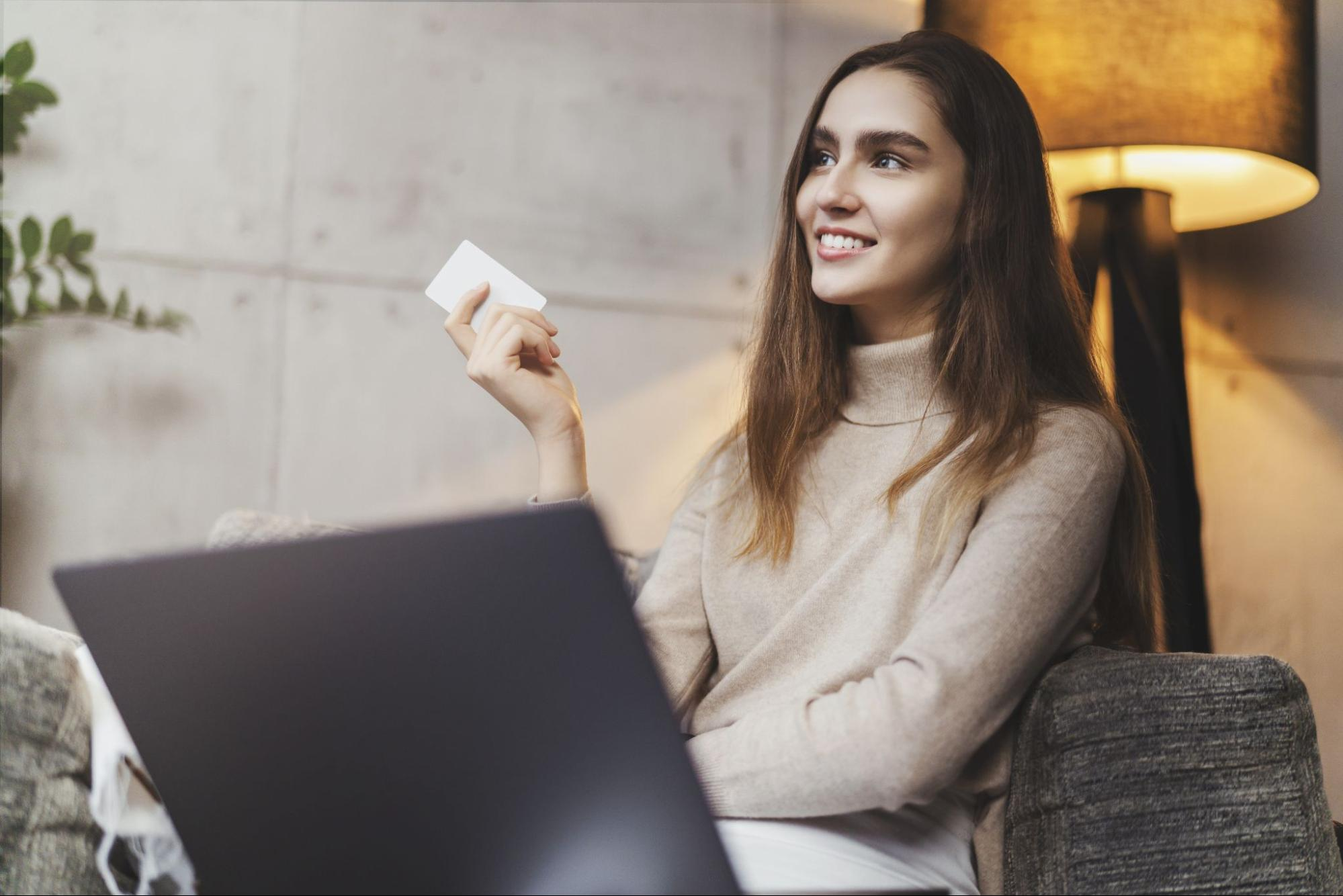 customer retention software: Woman smiling while sitting on a couch and holding a card