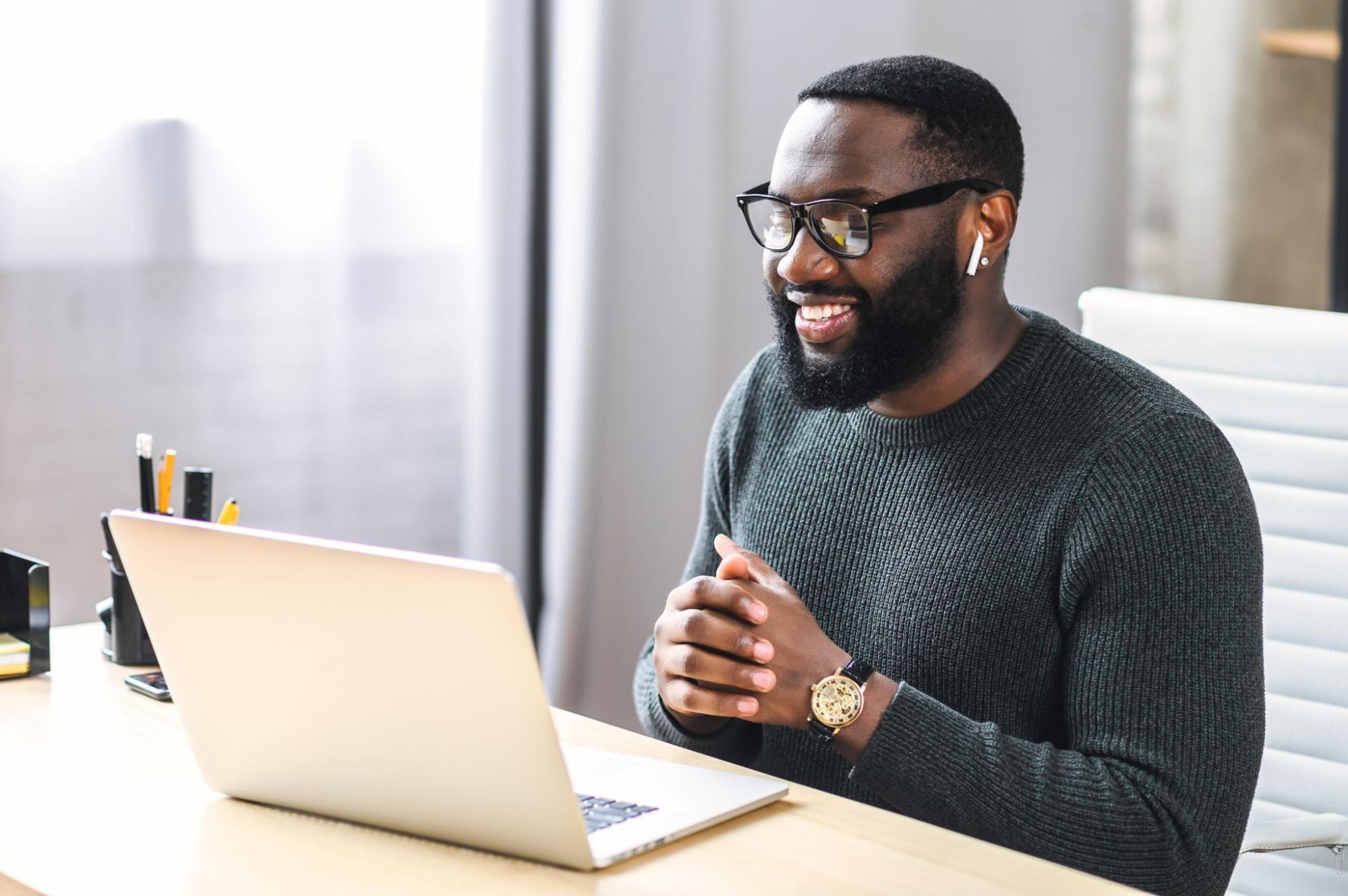 customer retention software: Smiling man looking at his laptop
