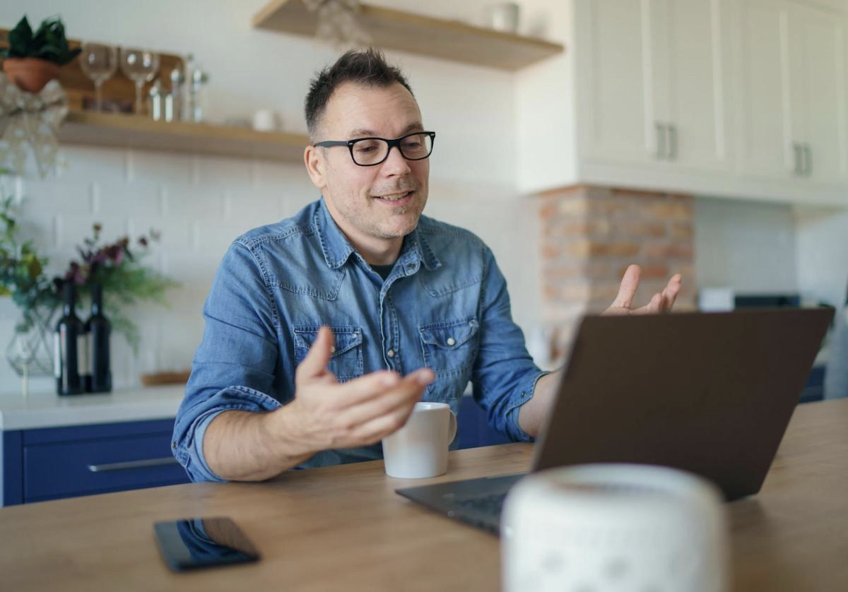 SaaS sales funnel: Smiling man talking in front of his laptop
