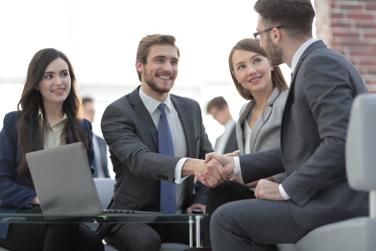 client vs customer: Two men smiling while shaking hands
