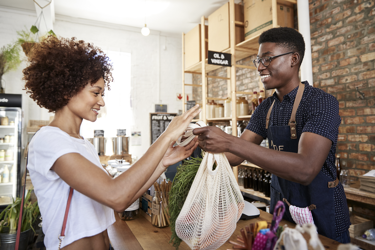 client vs customer: Vendor handing purchased items to the customer