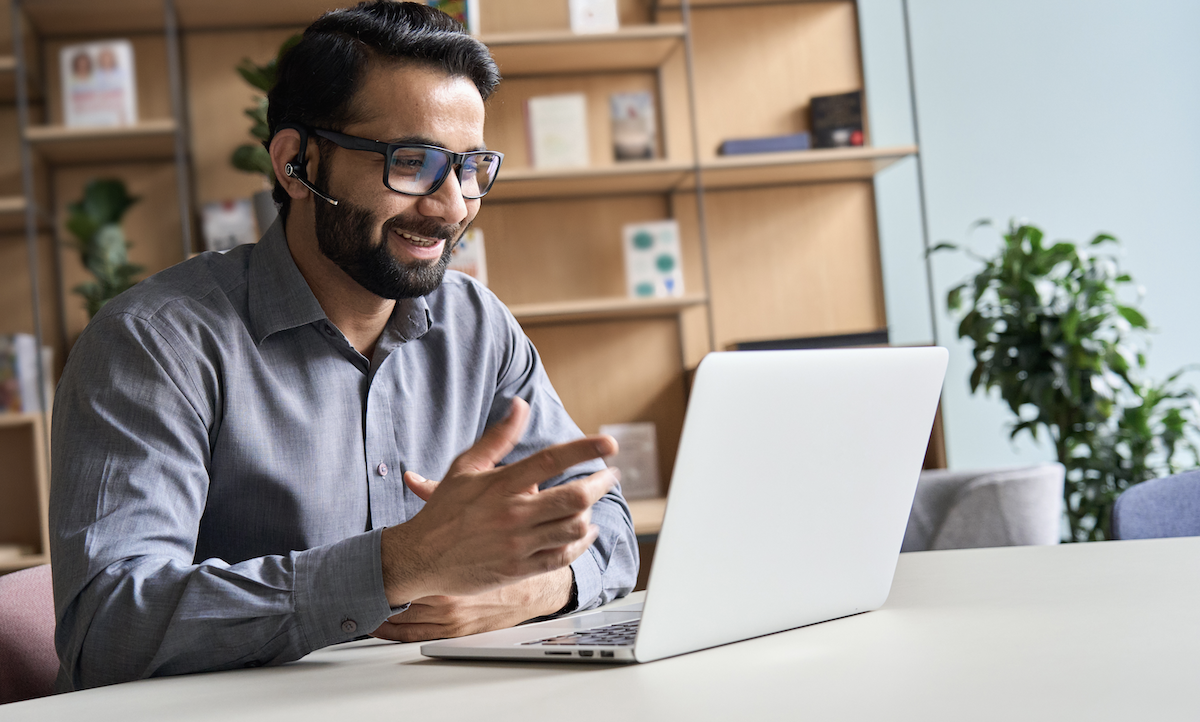 customer onboarding software: Smiling man using his laptop for a video call