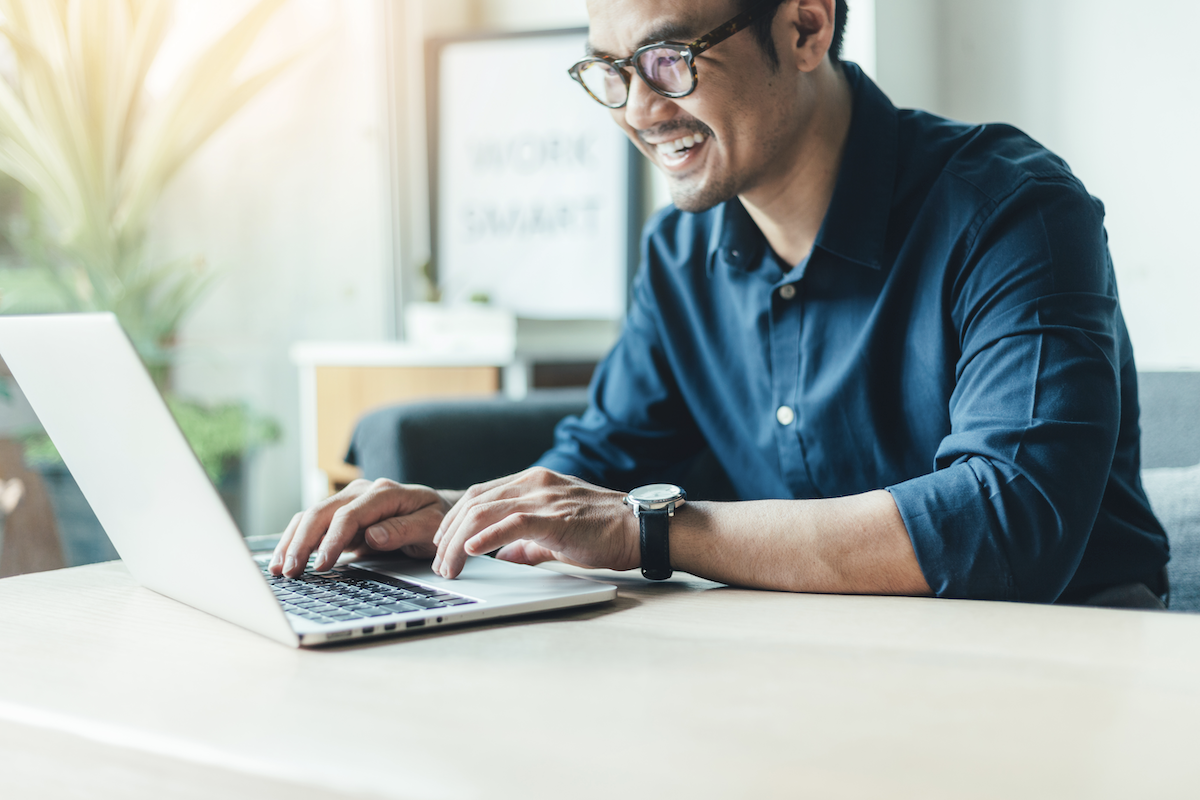 product tour: Smiling man using his laptop