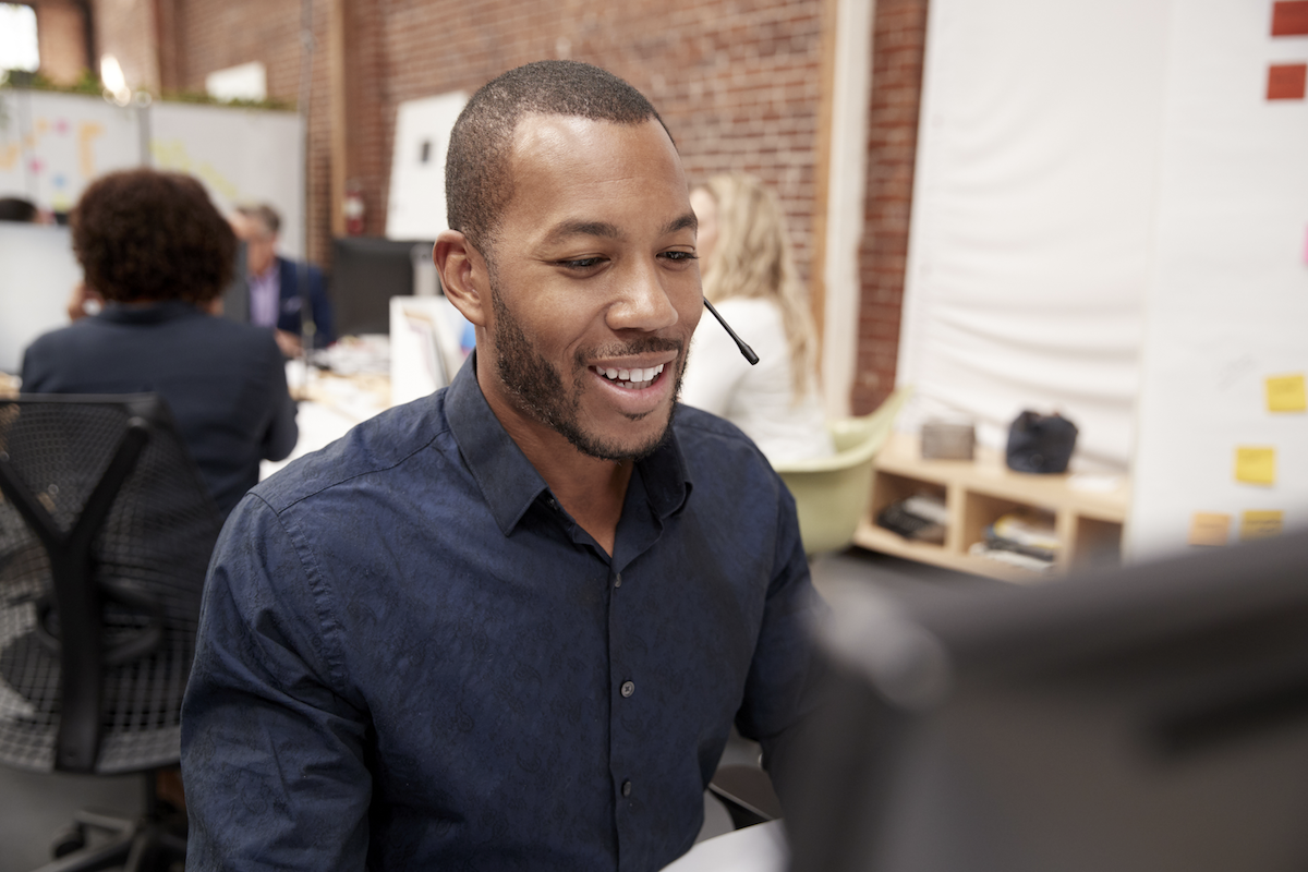sales enablement app: Smiling man using his computer while on a call