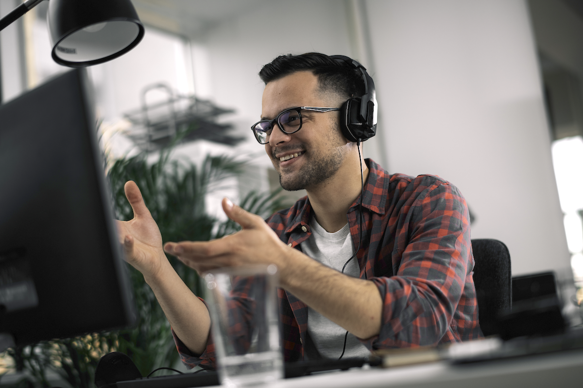 sales enablement app: Smiling man wearing headphones on and doing hand gestures in front of his computer