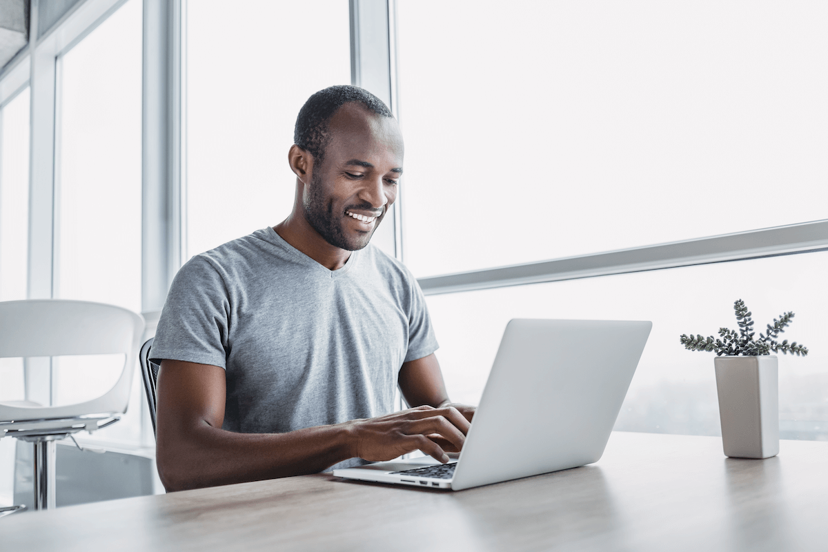 sales management software: man happily working on his laptop