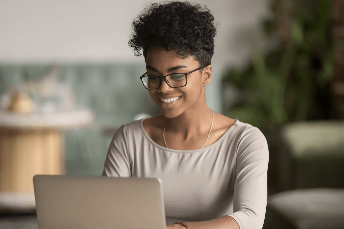 sales management software: woman happily working on his laptop