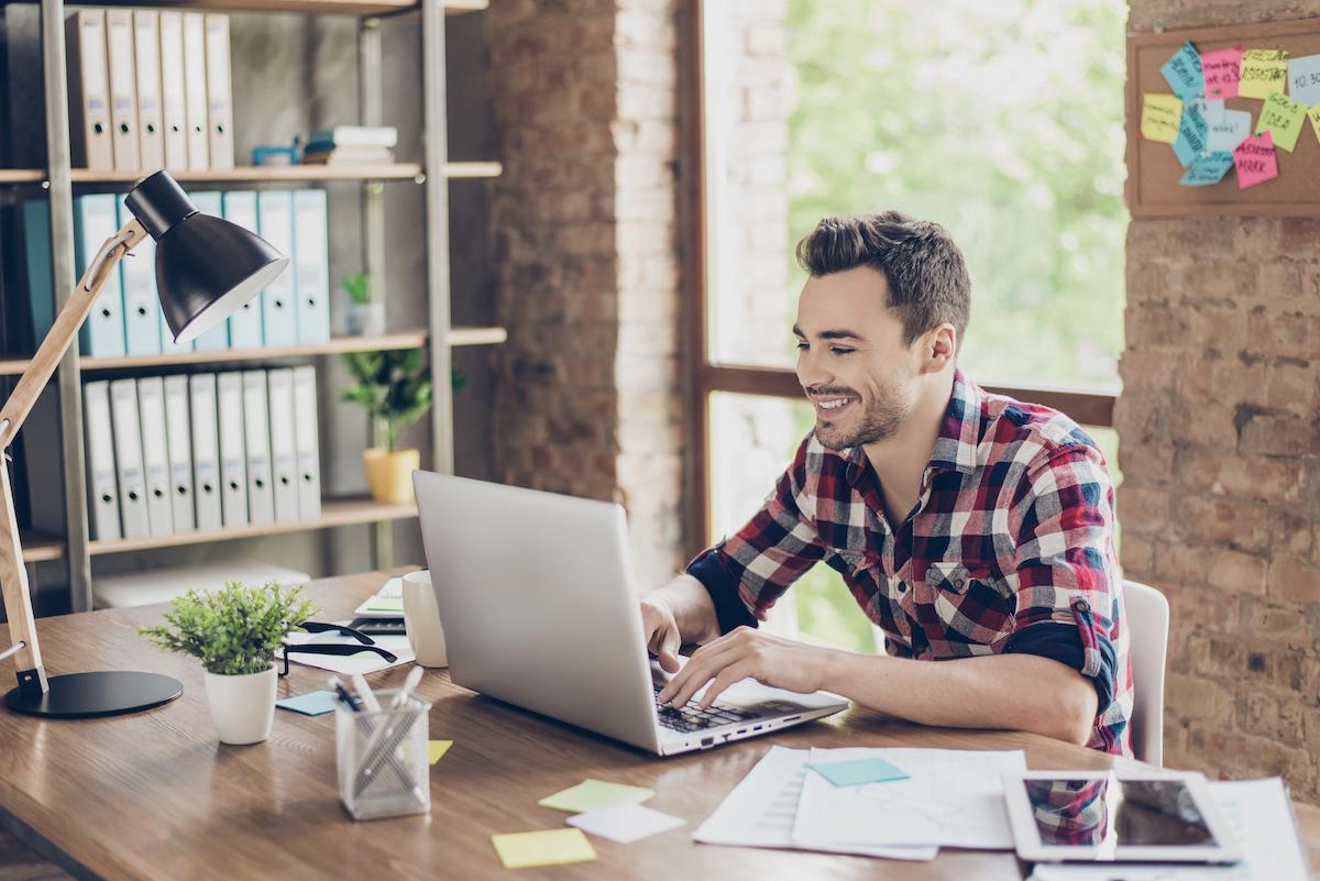 customer engagement software: Smiling man using his laptop