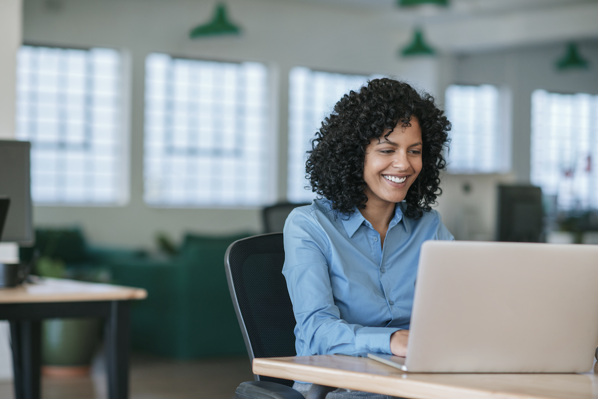 customer engagement software: Smiling woman using her laptop