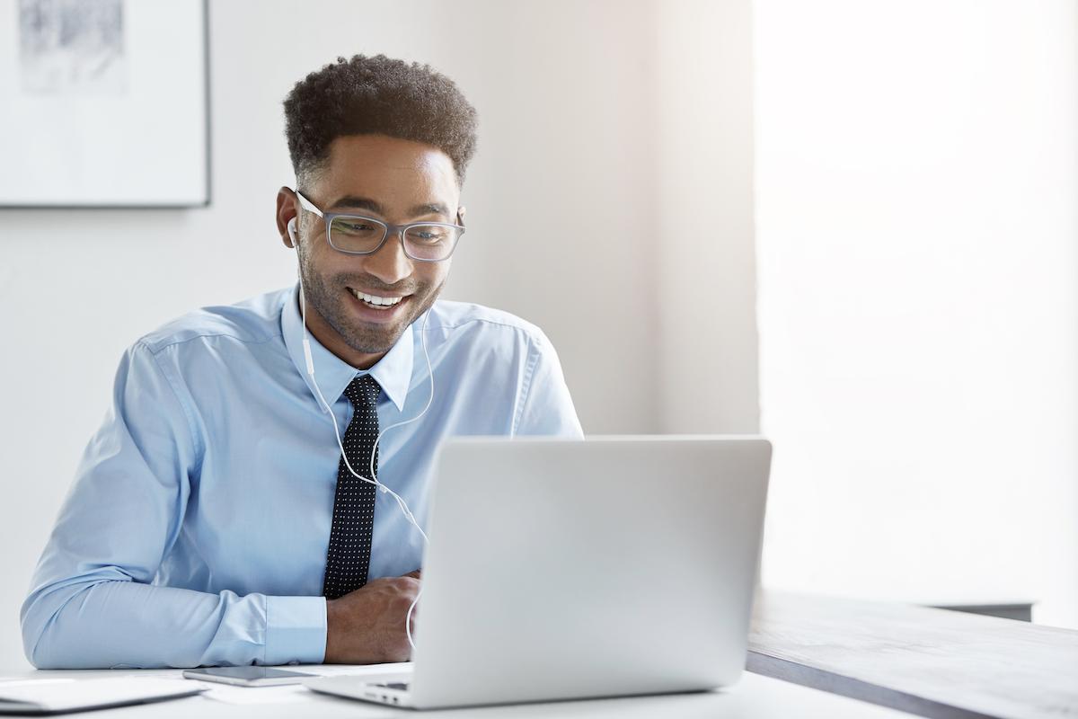 sales methodology: Smiling man wearing earphones and looking at his laptop