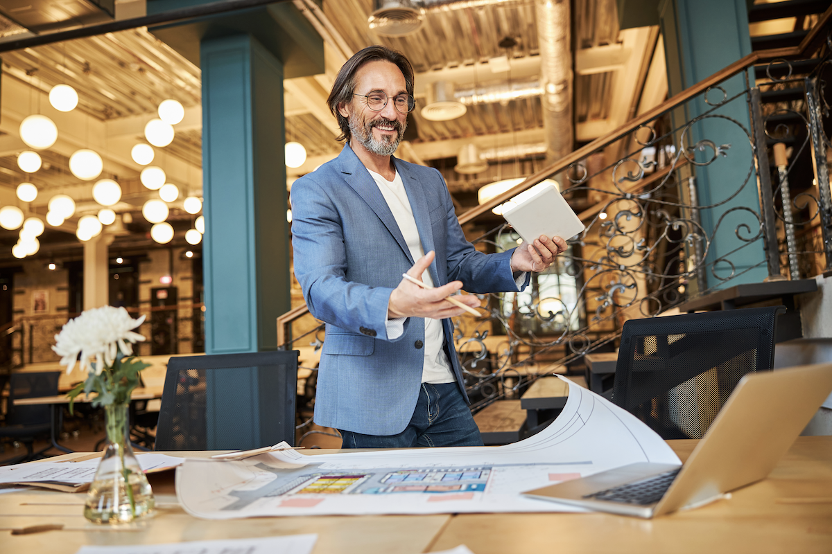 sales methodology: Smiling man doing hand gestures while looking at his laptop