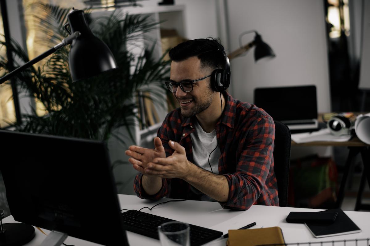 growth marketing: Smiling man talking to someone on his laptop while wearing headphones