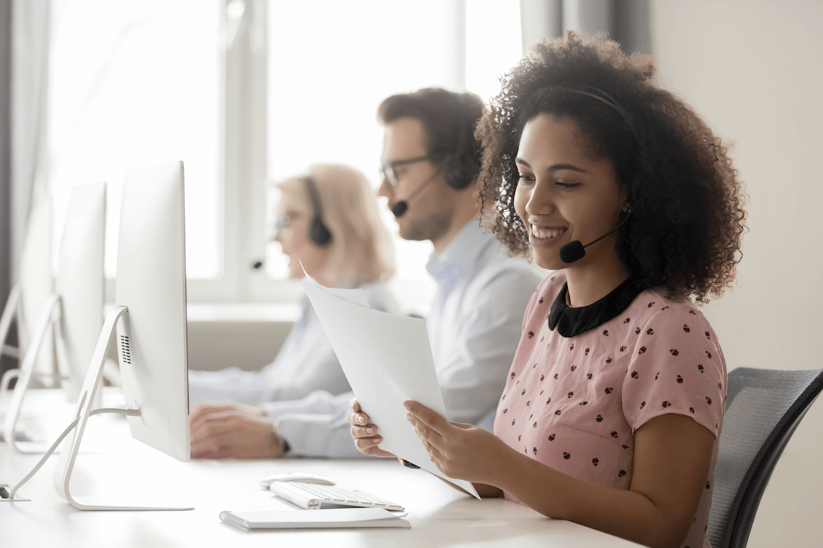SPIN selling: Smiling woman wearing a headset while reading a document