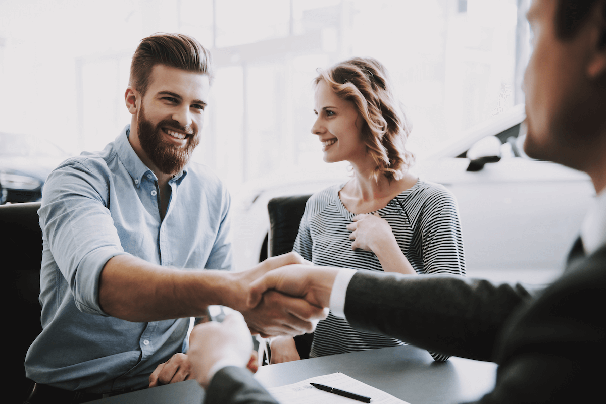SPIN selling: Smiling woman looking at two men shaking hands