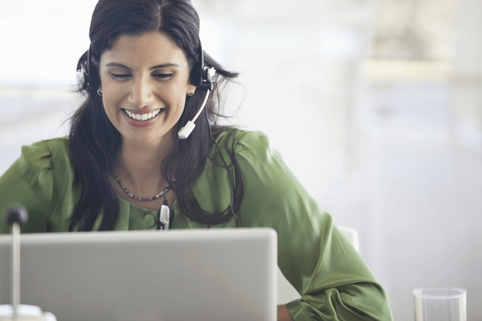 Woman wearing a headset and smiling while looking at her laptop