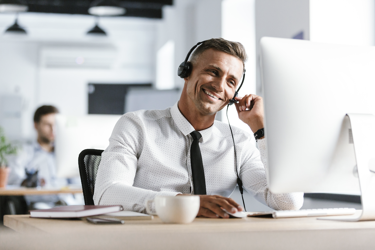 lead response: Smiling man wearing a headset while looking at his monitor